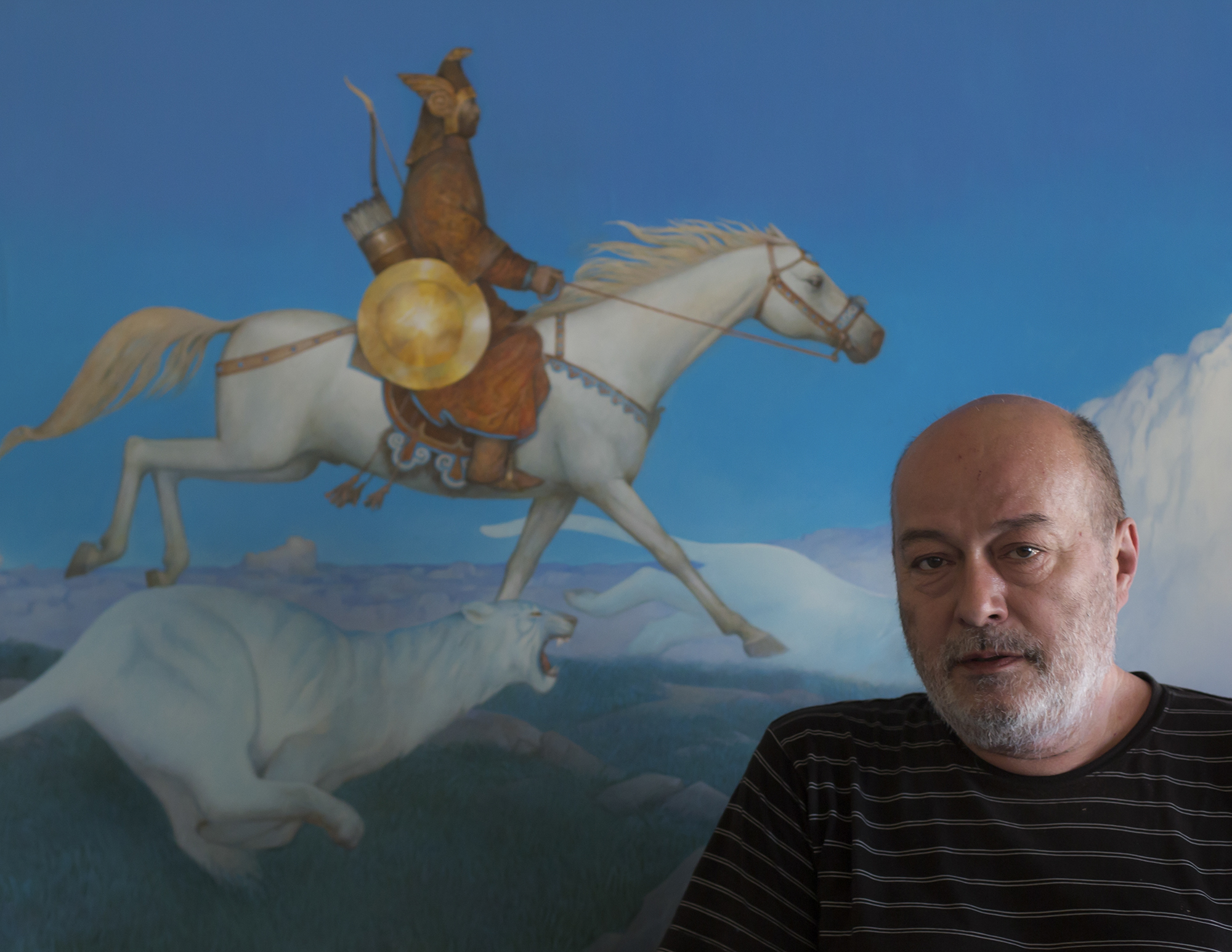 Азат Миннекаев на фоне работы Охота Тенгри с небесными тиграми. 2010. Холст, акрил, темпера. 80х140 см. Коллекция Фонда Марджани.JPG